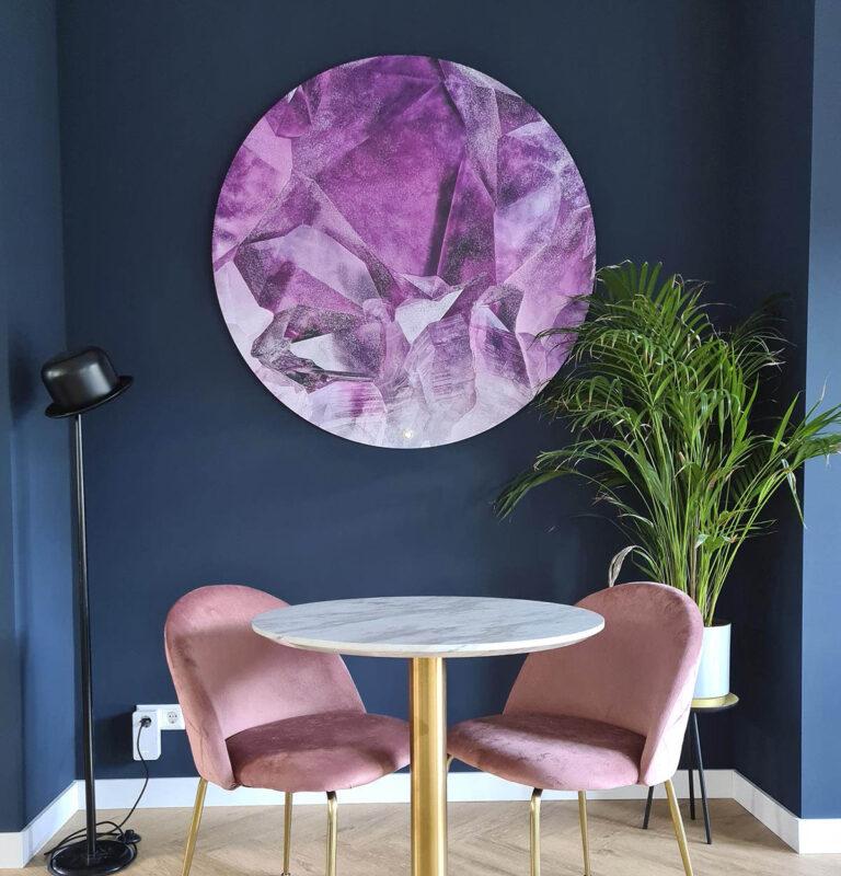 Woonkamer met wandcirkel met roze kristallen erop uitgebeeld.