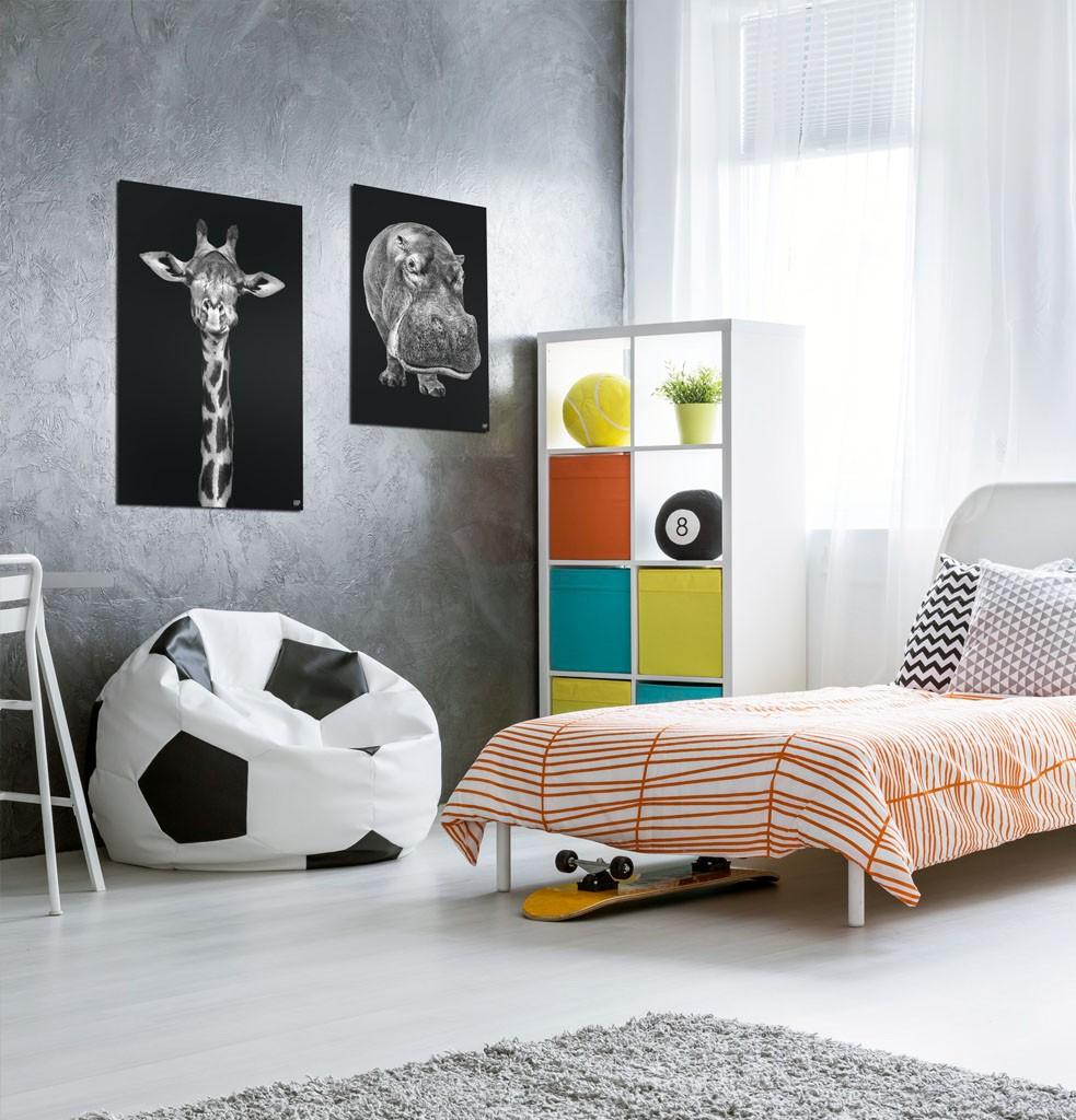 Kinderslaapkamer met twee vierkante wanddecoraties van dieren in het zwart-wit erop.