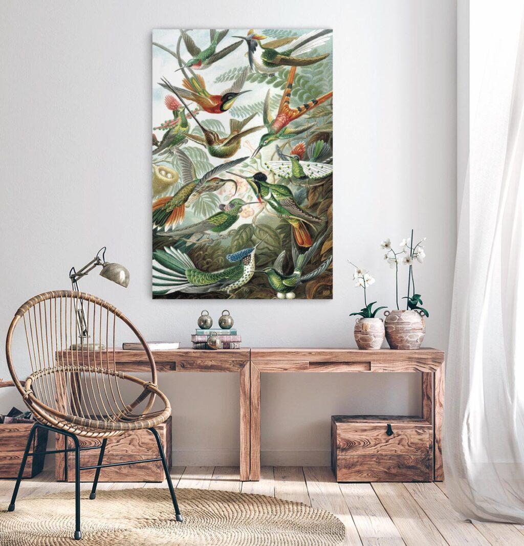Woonkamer met houten tafel met daarboven een vierkante wanddecoratie met daarop verschillende vogels op afgebeeld.