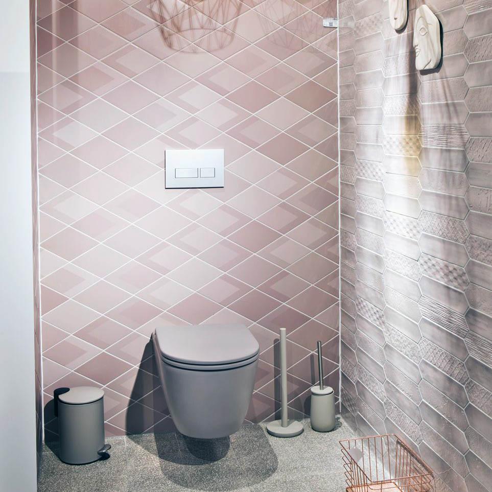 Toilet met roze en paarse tegels in verschillende vormen aan de muur.