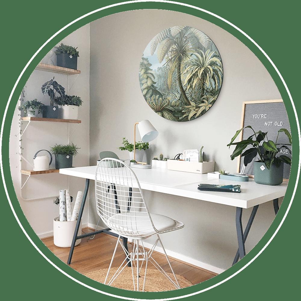 Thuiswerkplek met een wit bureau en stoel met erboven een wandcirkel van de jungle erop.
