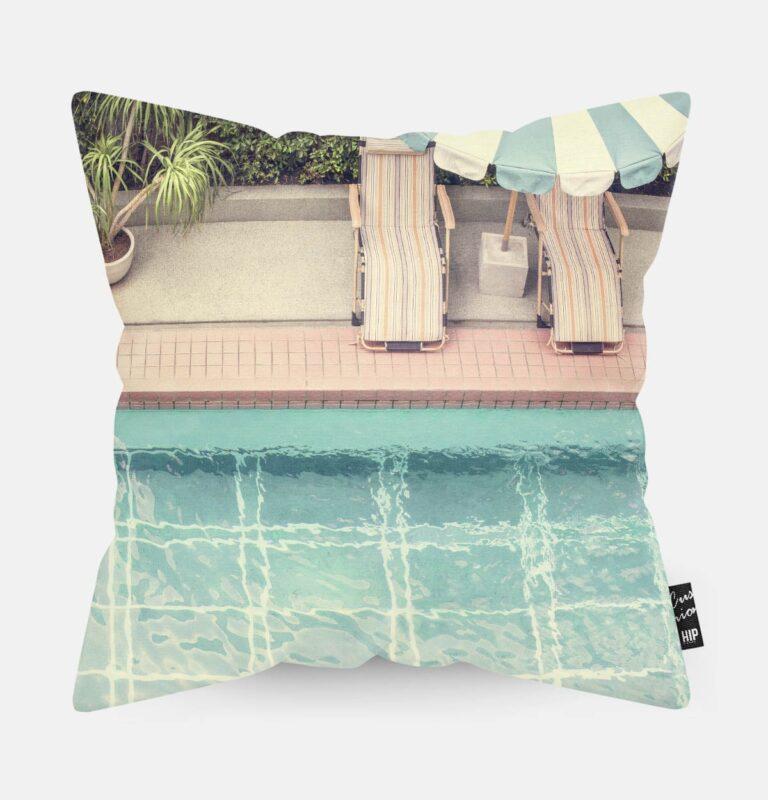 Kussen met een zwembad met strandbedden erop afgebeeld.
