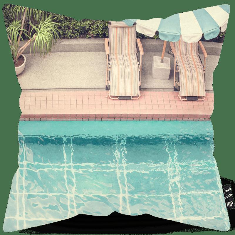 Kussen met een zwembad en zonnebedden ernaast op afgebeeld.
