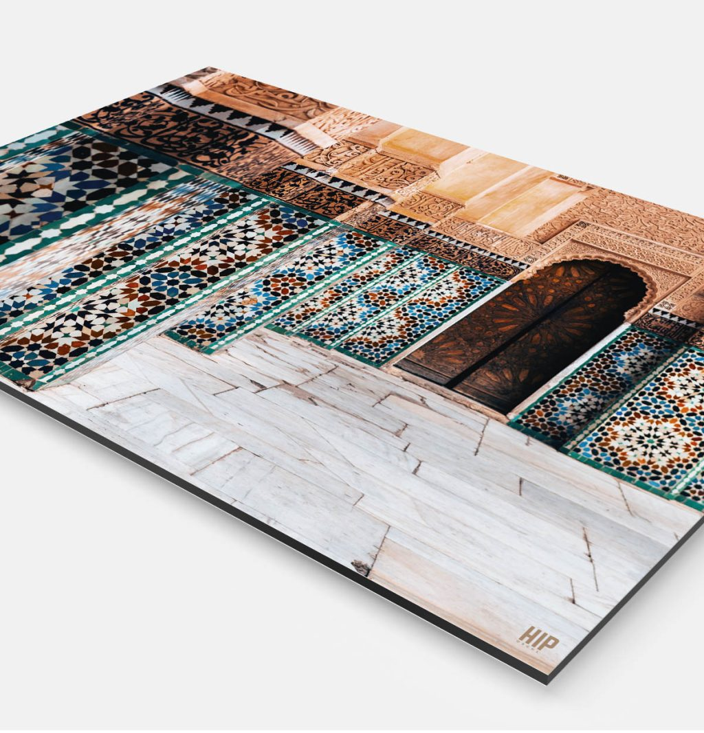 Vierkante wanddecoratie met een gebouw in Marrakesh erop afgebeeld.