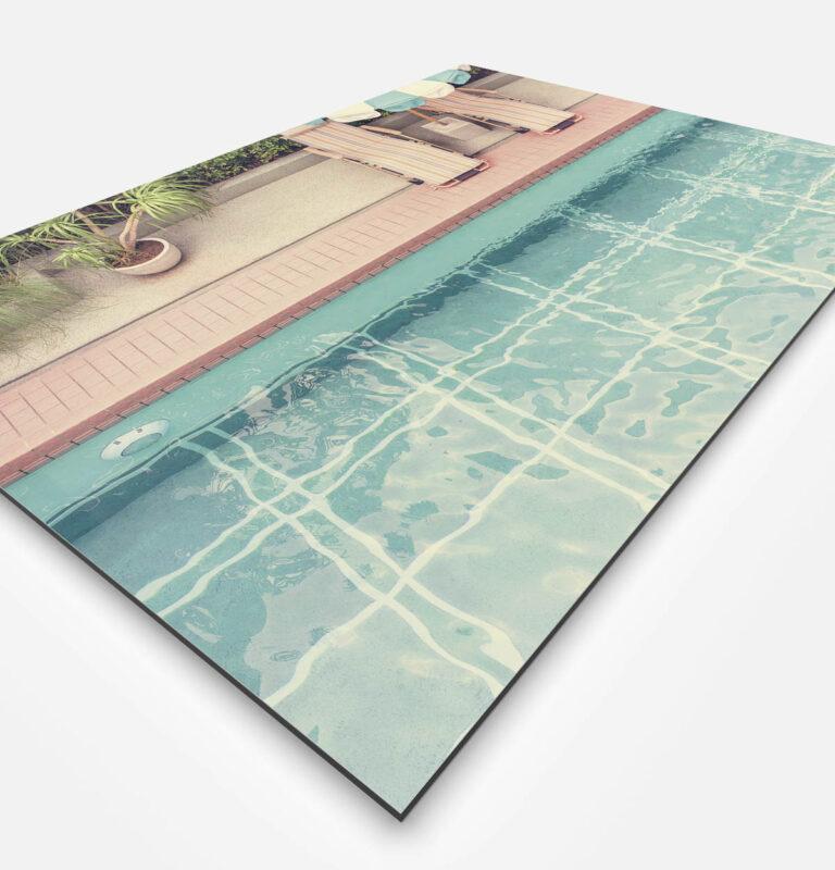 Vierkante wanddecoratie van een zwembad met bedden aan de rand.