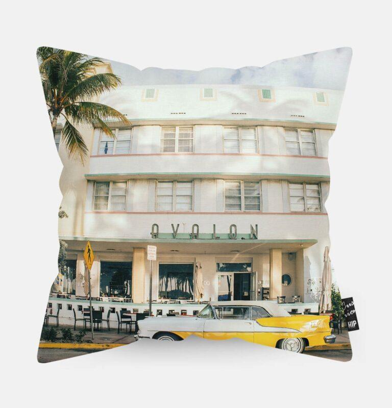 Kussen met een gele luxe auto voor een hotel erop.