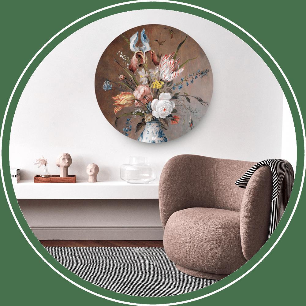 Een woonkamer met bruine zitstoel en aan de witte muur een ronde decoratie van een bloemen in lichtblauwe vaas