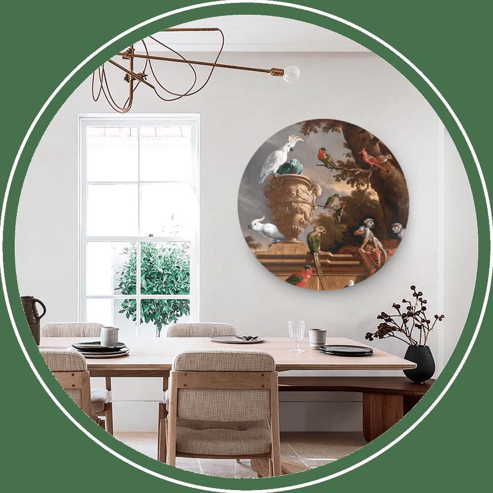 Een eetkamer met houten tafel met rechts daarboven een ronde wanddecoratie met verschillende vogels.