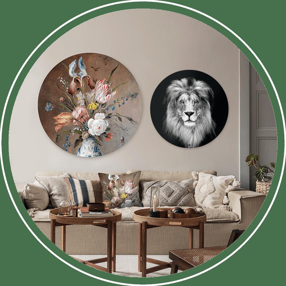 Een woonkamer met lichte bank en twee ronde wanddecoraties. Links bloemen in een vaas en rechts een leeuw in het zwart-wit.