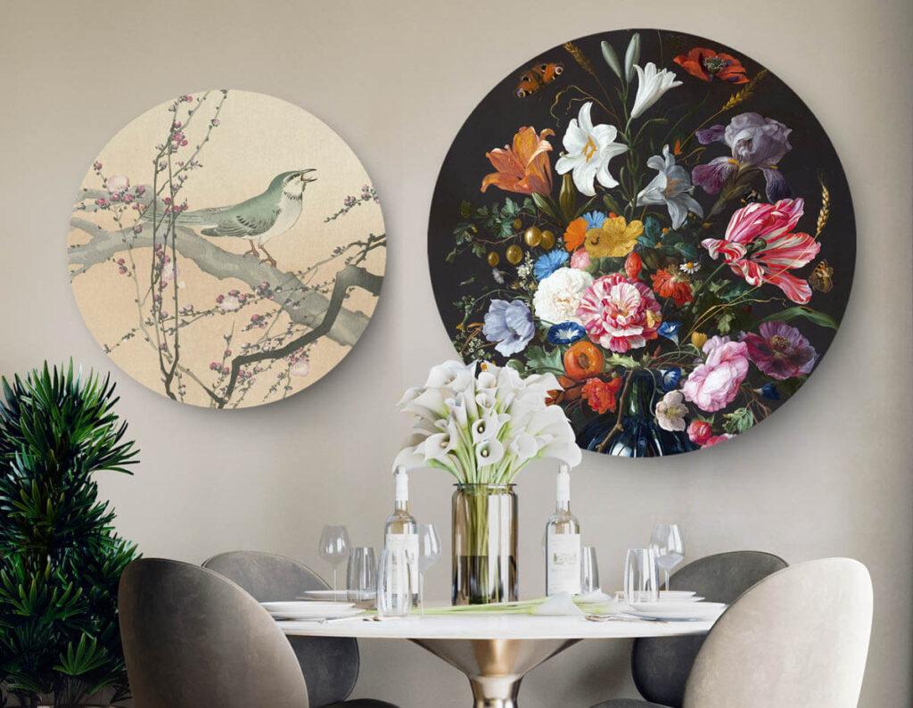 Een eetkamer met ronde tafel en vier stoelen met daarboven 2 ronde wanddecoraties. Links van een vogel en rechts een kleurrijke vaas