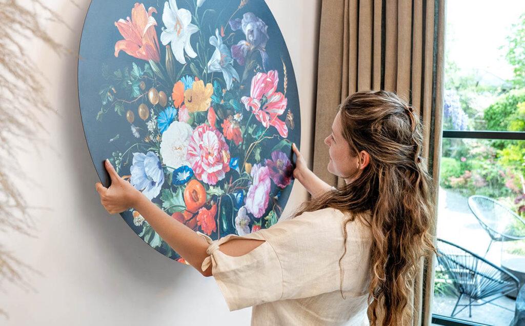 Een mevrouw die demonstreert hoe makkelijk een ronde wanddecoratie ophangt aan de muur.